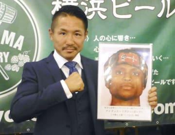 王者アイザック・ドグボエの写真を手にポーズをとる大竹秀典=31日、横浜市