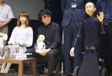 大阪大の石黒浩教授と並ぶ女性型ロボット「ERICA(エリカ)」(左)、子供型の「ibuki(イブキ)」(右)=31日午後、東京都江東区