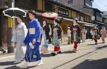 京都・祇園の夏の恒例行事「八朔」で、強い日差しの中あいさつ回りをする芸妓や舞妓ら=1日午前