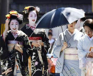 厳しい暑さが続く中、京都・祇園の夏の恒例行事「八朔」で、あいさつ回りをする芸妓や舞妓ら=1日午前