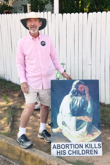 イエス・キリストの肖像画と「中絶は彼の子を殺す」と書かれた看板を持って中絶手術に抗議するロン・ニダーフッドさん=6月27日、米南部ジャクソン(共同)