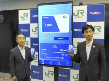 みずほ銀行の口座から直接入金できるアプリについて説明する、みずほ銀とJR東日本の担当者=1日午前、東京都千代田区
