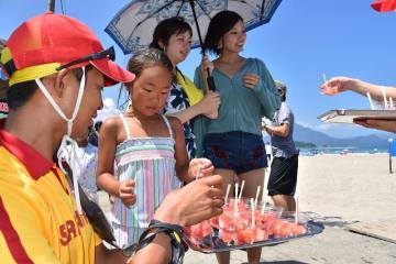海水浴客にスイカを配るライフセーバー=7月31日、福井県高浜町和田の若狭和田海水浴場