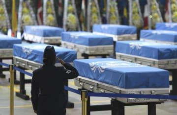 遺骨返還の記念式典で敬礼する軍人=1日、ソウル南方の烏山米空軍基地(共同)