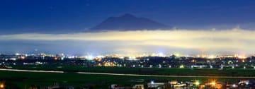 夜景がきれいな弘前市の上空に濃霧が現れ、浮かんで見えた岩木山=1日午前1時半ごろ、弘前市薬師堂(長時間露光)