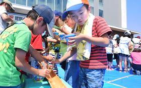 竹を流れる麺を夢中でキャッチする子どもたち