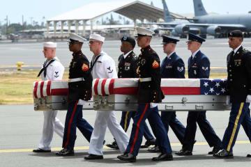 1日、米ハワイのヒッカム空軍基地で、米兵の遺骨が入ったひつぎを運ぶ兵士ら(ロイター=共同)