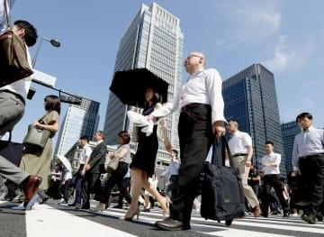 厳しい暑さの中、日傘やタオルを手にJR東京駅前を歩く人たち=2日午前8時22分