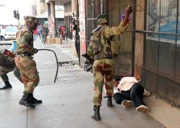 1日、ジンバブエ・ハラレの野党、民主変革運動(MDC)の本部前で、支持者をたたきつける兵士ら(ロイター=共同)