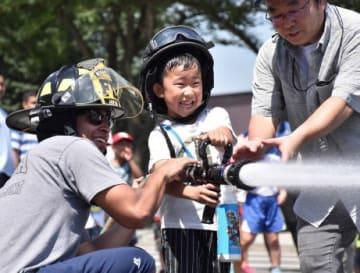 消防士になりきり放水体験をする子ども