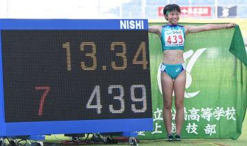 陸上女子100メートル障害 高校新の13秒34で優勝し、タイム表示の前で笑顔を見せる市船橋・小林歩未=2日、三重交通Gスポーツの杜伊勢陸上競技場
