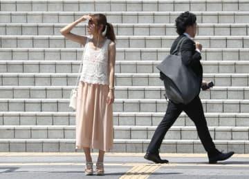 猛暑が続く名古屋市内で、強い日差しを手で遮る女性=3日午前