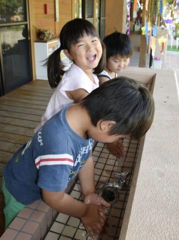 断水していた愛媛県宇和島市三間町地区で試験通水が始まり、蛇口から出る水に喜ぶ園児たち=3日午後