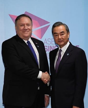 握手するポンペオ米国務長官(左)と中国の王毅国務委員兼外相=3日、シンガポール(ロイター=共同)