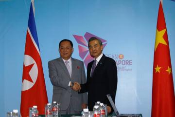 握手を交わす北朝鮮の李容浩外相(左)と中国の王毅国務委員兼外相=3日、シンガポール(ロイター=共同)