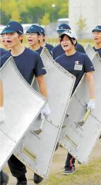 盾の重さに顔をゆがめてグラウンドを走る筆者=7月24日、名取市愛島の宮城県警察学校