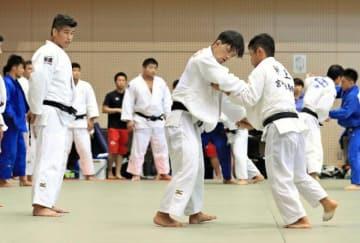 大野将平(中央)の練習を見守る井上康生監督(左)