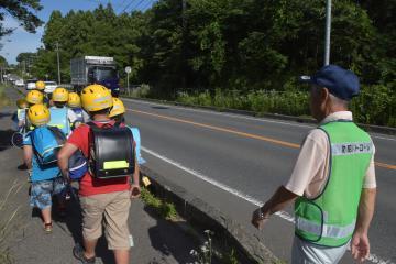 遺棄現場近くの国道293号を家路に向かう児童たち。見守り活動は現在も続く=常陸大宮市東野