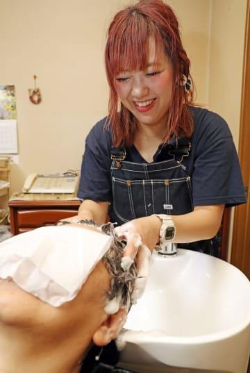 客と和やかに会話しながらシャンプーする美容師の宮崎さん=長崎市内
