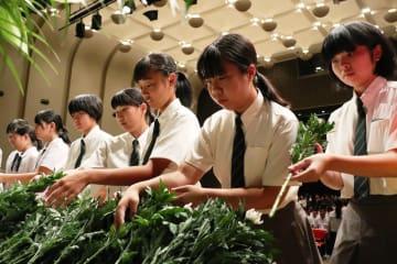 犠牲者へ追悼の意を込めて献花する生徒=長崎市平和会館