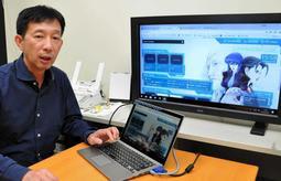新たなセキュリティーソフトの開発に加わった神戸大の小沢誠一教授。テレビの画面はソフトのサイト=神戸市灘区六甲台町