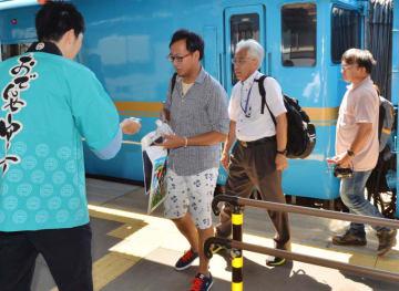 宮古駅に到着し宮古市職員らから地域の特産品を受け取る乗客