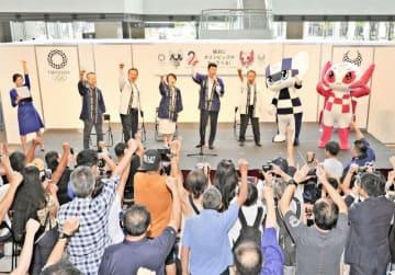 2年後に迫った東京五輪を盛り上げようと大会マスコットと一緒にガッツポーズを決める三浦さん(中央)ら=横浜市西区