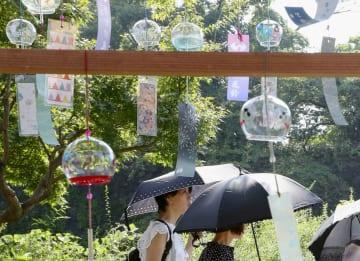 猛暑が続く名古屋市内で日傘を差して歩く人たち=4日午後