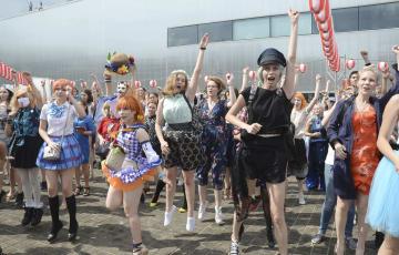 4日、モスクワ中心部で開かれた日本の夏祭りをテーマにしたイベントで、盆踊りの振り付けに盛り上がるコスプレ姿のロシア人ら(共同)