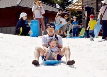 雪山でそり遊びを楽しむ来場者=8月4日、福井県勝山市の長尾山総合公園