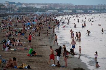 日没後も多くの人でにぎわうスペイン東部バレンシアの海水浴場=4日(ロイター=共同)