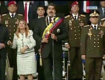 4日、カラカスで軍の行事の最中、音に反応し上方を見るマドゥロ大統領(中央)らのビデオ映像(ベネズエラ国営テレビ提供、ロイター=共同)
