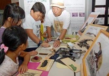 長田支部長(右)の手ほどきを受けて作品を仕上げる子どもら=4日、境港市の夢みなとタワー