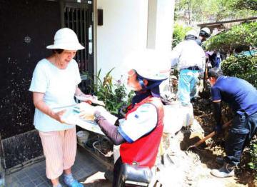 バイクで入れない路地を歩き、女性(左端)に郵便物を手渡す配達員(3日、広島県坂町小屋浦3丁目)