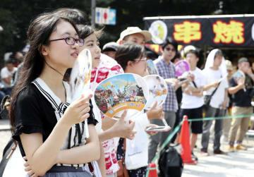 最高気温が39.9度を記録した名古屋市内で、うちわを使って涼を求める人たち=5日