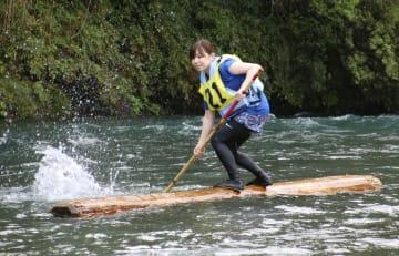 木頭杉一本乗り大会で丸太に乗る参加者=5日午後、徳島県那賀町
