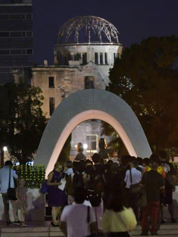 原爆投下から73年の「原爆の日」を前に、慰霊碑前で手を合わせる人たち。奥は原爆ドーム=5日夕、広島市の平和記念公園