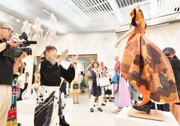 開幕した企画展で展示された洋服を説明するコシノヒロコさん(左から2人目)=8月5日、福井県鯖江市まなべの館