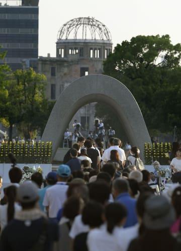 原爆の日を迎え、慰霊碑前で手を合わせる大勢の人たち。奥は原爆ドーム=6日早朝、広島市の平和記念公園