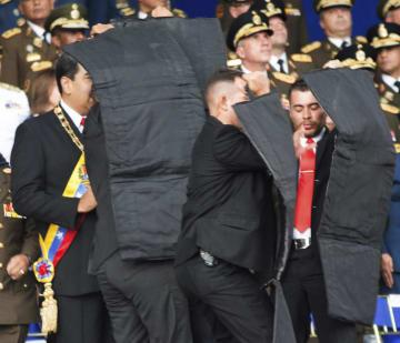 4日、カラカスの式典でドローンの爆発が起きた際に、演説していたマドゥロ大統領(左端)を取り囲み護衛する警護要員(新華社提供、AP=共同)