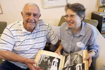 1964年の東京五輪期間中に挙げた結婚式のアルバムを手にするニコライ・プロダノフさん(左)とディアナさん=4月、ブルガリア・ソフィア(共同)