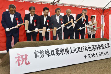 JR東日本の常磐線双葉駅の起工式で、くわ入れをする関係者=6日午前、福島県双葉町
