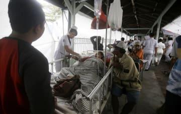 6日、インドネシア・バリ島で、地震発生を受けて病院の外に避難した患者(AP=共同)