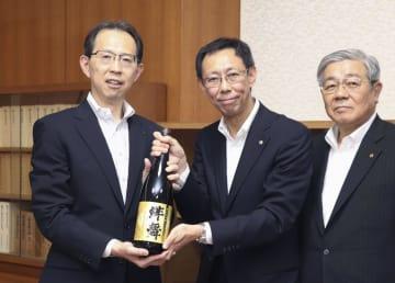完成した日本酒「絆舞」を贈呈される福島県の内堀雅雄知事(左)=6日午後、福島県庁