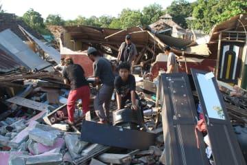 6日、インドネシア・ロンボク島北部で、地震で崩壊した建物から持ち物を捜す住民ら(ゲッティ=共同)