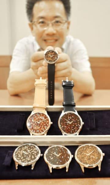 伝統工芸の若狭塗を文字盤に用いた腕時計を示す小泉伊久治社長