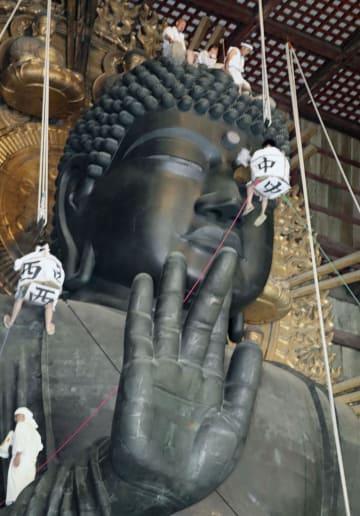 奈良・東大寺でゴンドラを使って行われた、大仏のほこりを払う「お身拭い」=7日午前