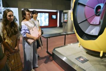 長崎市の原爆資料館で原爆の模型を見つめるブルーク・ボルトンさん(左)ら=7日午前