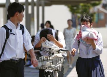 猛暑が続く岐阜県多治見市のJR多治見駅前で汗を拭う生徒たち=3日