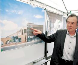 再整備する双葉駅の完成予想図を指し示す伊沢町長=福島県双葉町